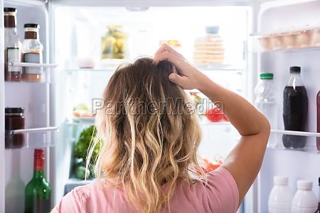 donna confusa che osserva in frigorifero