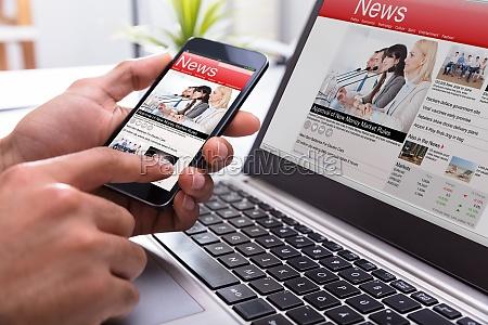 businessperson holding smartphone con notizie online