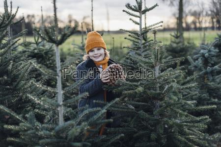 little boy standing among fir trees