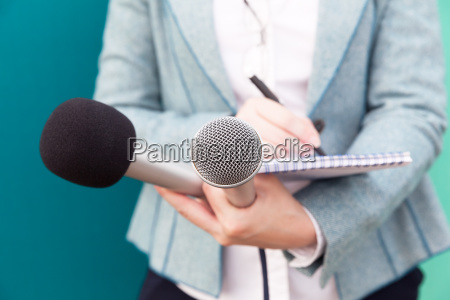 female journalist at news conference writing
