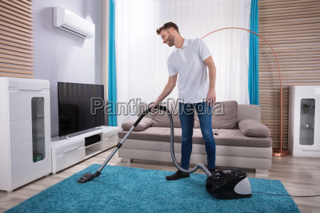 man cleaning carpet with vacuum cleaner