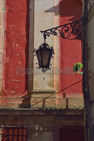 ornate street light against red wall