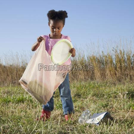 giovane ragazza raccogliendo i rifiuti