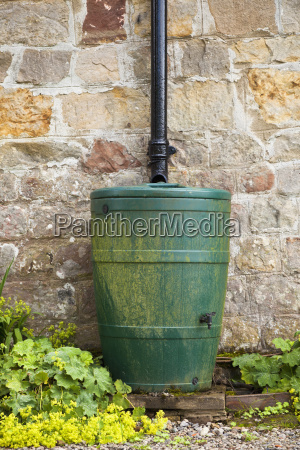 water barrel by stone wall
