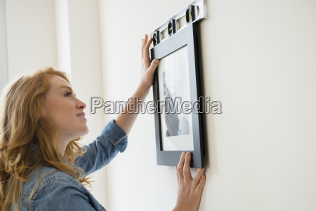 woman hanging picture on wall