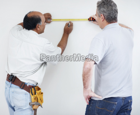 men measuring wall