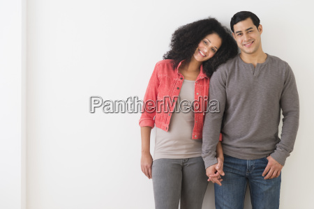 portrait of smiling couple standing against