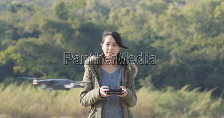 woman control flying drone at outdoor