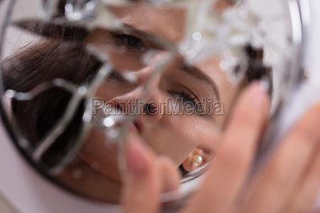 womans face in broken mirror