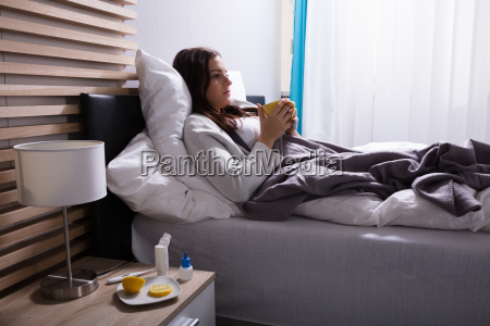 sick woman drinking cup of tea