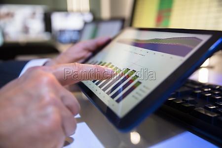 businessperson guardando grafico finanziario su tablet
