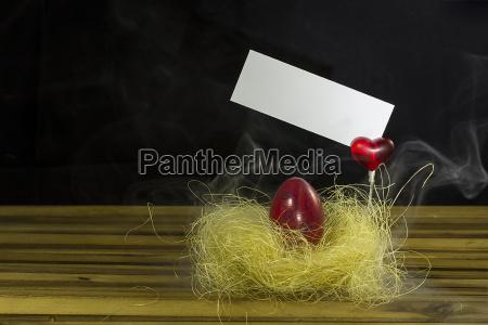 osterei im nest mit rotem herz