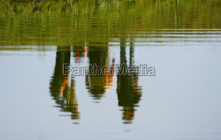 reflection of three people in a