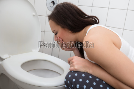 woman vomiting in toilet bowl