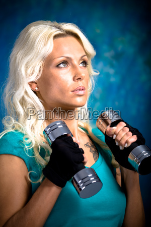 young woman with dumbbells during fitness