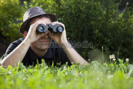 young man is lying with binoculars
