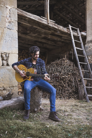 young man playing guitar outdoors on