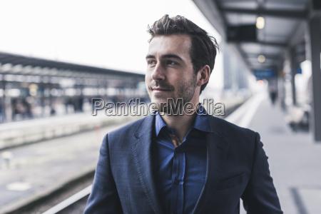 young businessman waiting at station platform