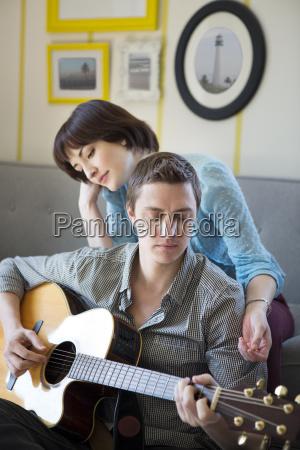 woman listening to boyfriend playing guitar