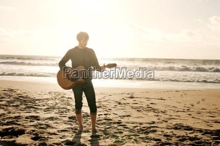 man playing guitar while standing at