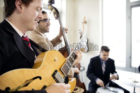 smiling men practicing in music studio