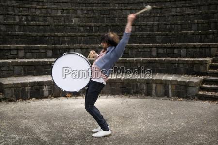 full length of man playing drum