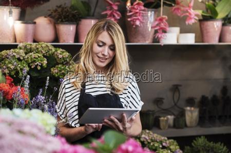 fiorista che utilizza computer tablet nel