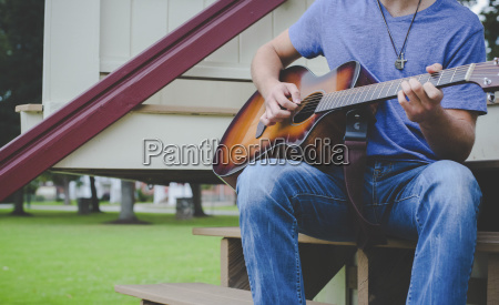 midsection of man playing guitar while