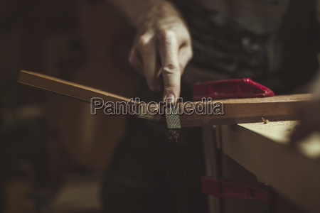 midsection of man shaving wood at