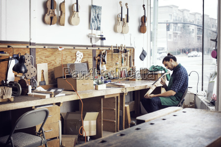 man making violin while working in