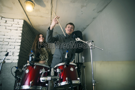 portrait of friends playing drum kit