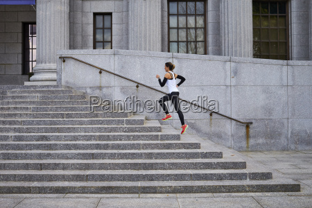 female jogger running up steps of