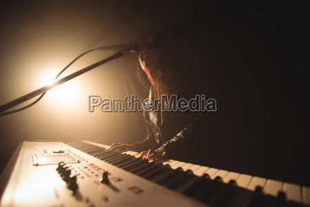 female singer playing piano while performing