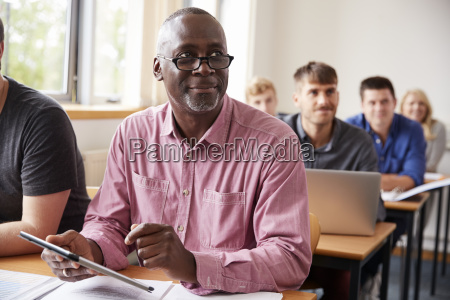 mature student using digital tablet in
