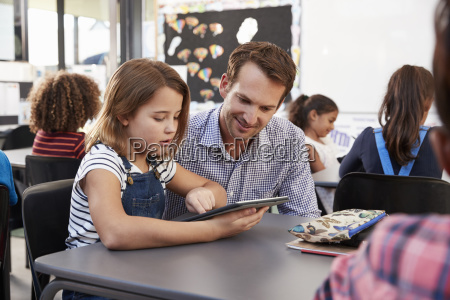 teacher and young schoolgirl using tablet