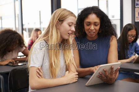 teacher helps blonde teenage schoolgirl with