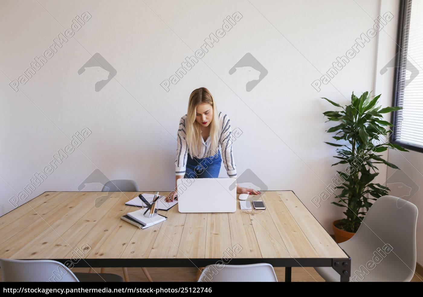 giovane, imprenditrice, in, piedi, alla, scrivania, utilizzando - 25122746