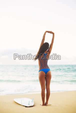 beautiful surfer girl stretching on the
