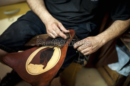 a craftsmans hands working on leather