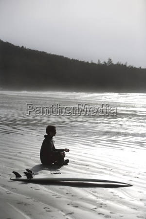 surfer meditating on beach cox bay