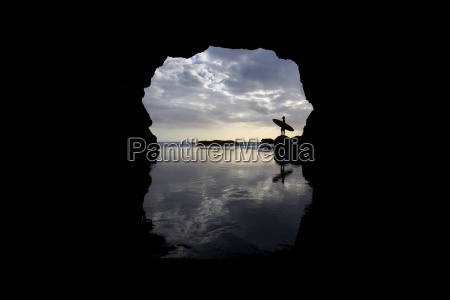 silhouette of surfer on beach through