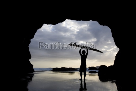 surfer inside a cave at muriwai