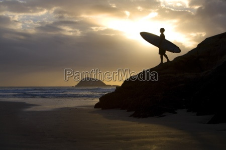 a surfer on muriwai beach new