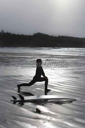 surfer stretching on beach