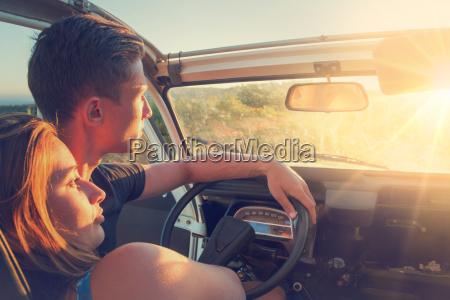 coppia in auto al tramonto