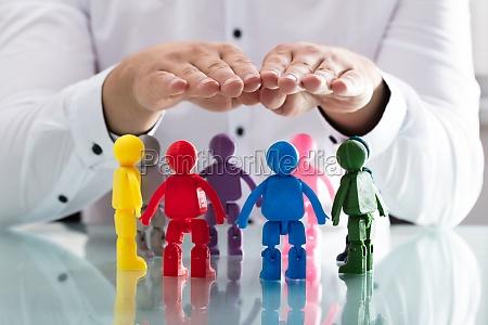 persona che protegge figure umane multicolore