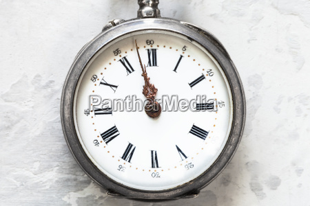 retro pocket watch on white concrete