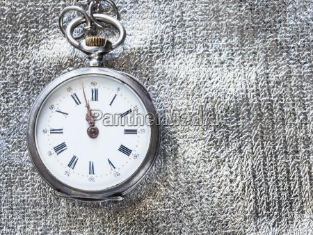retro pocket watch on silver textile