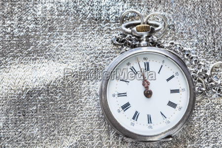 old pocket watch on silver textile