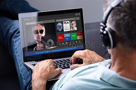 uomo guardando film su laptop